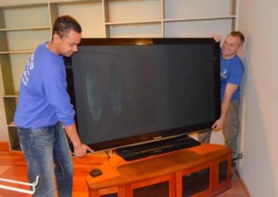 Pictured: professional movers moving a large tv.