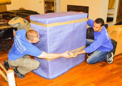 Pictured: professional movers moving a large piece of furniture.