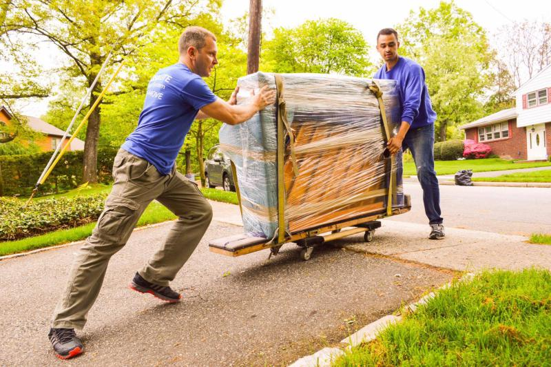 This is an image of professional movers moving some plastic wrapped furniture.